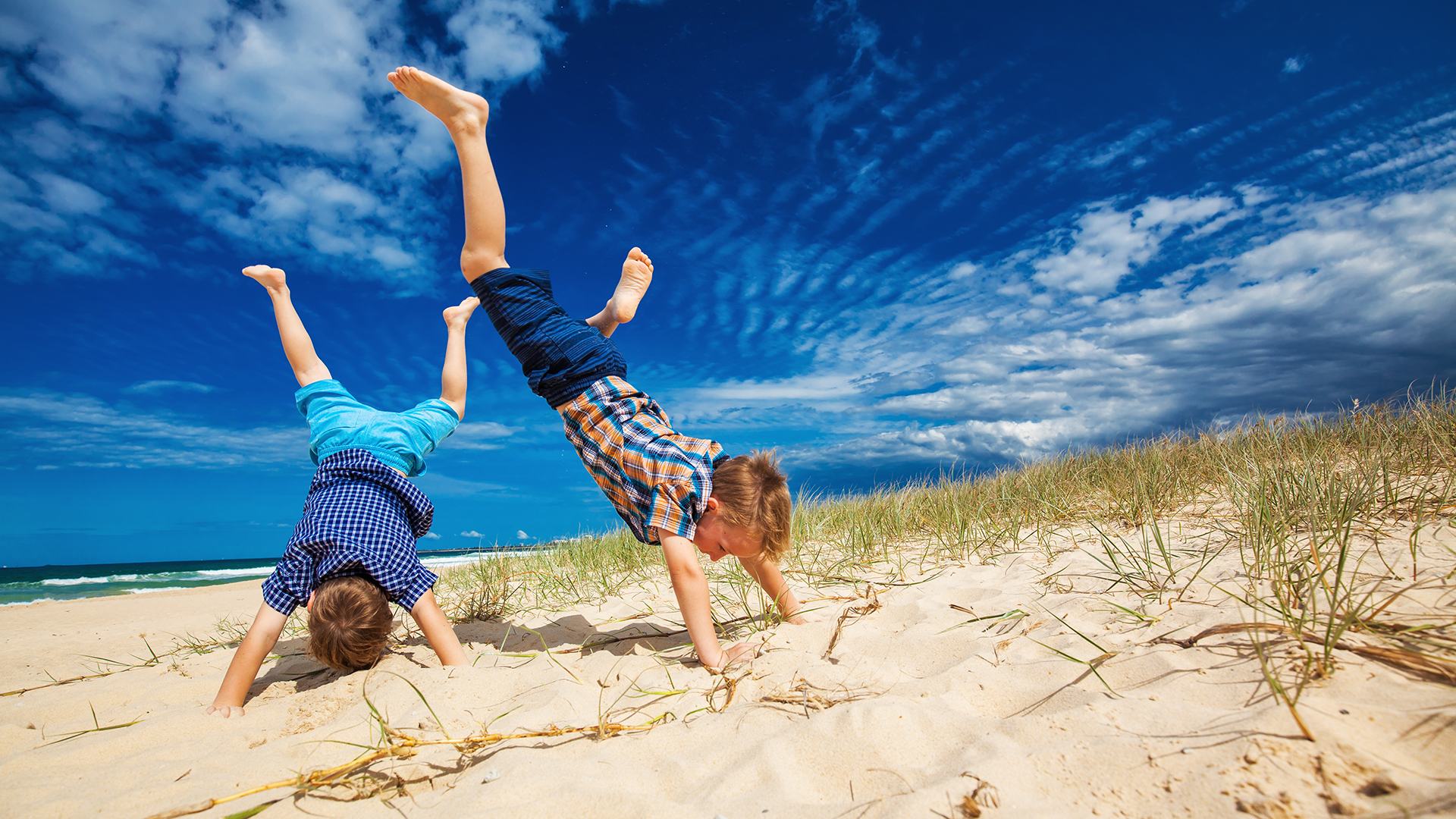 Young happy boys having fun on tropical beach, doing hand stands